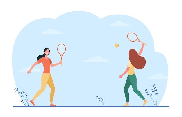 Glückliche frauen, die im badminton draußen spielen