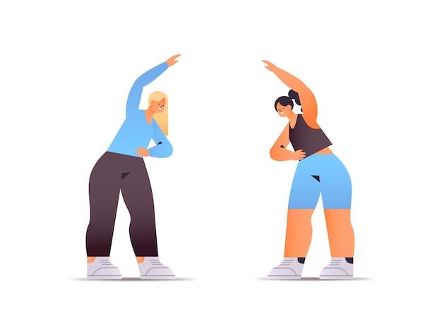 Glückliche frauen in der sportbekleidung, die dehnübungen macht gesundes lebensstilkonzept