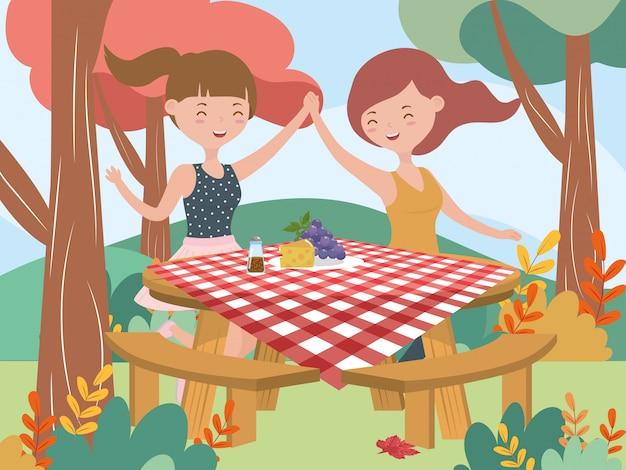 Glückliche frauen mit tabellenlebensmittel-picknicknaturlandschaft
