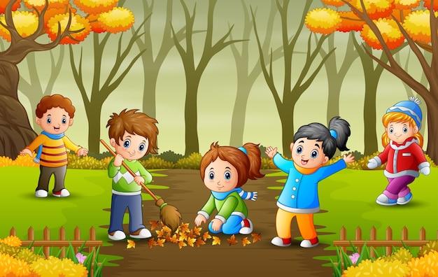 Glückliche freiwillige kinder, die herbstlaub im park aufräumen