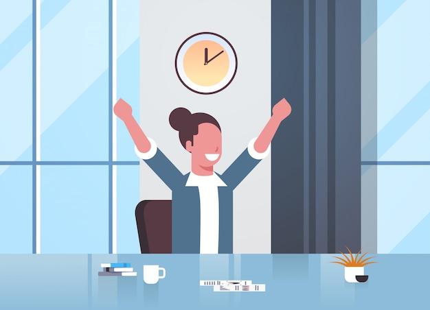 Glückliche geschäftsfrau, die hände erhebt, die erfolg effektives zeitmanagementkonzept-geschäftsfrau-sitzarbeitsplatz modernes büroinnenporträt horizontal ausdrücken