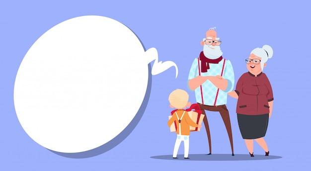 Glückliche großeltern-paare mit dem enkel, der anwesenden kasten modernen großvater und großmutter und kleinen jungen gibt