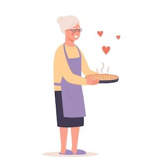 Glückliche großmutter mit heißem kuchen großmutter in gläsern schürze kuchen backen kochen