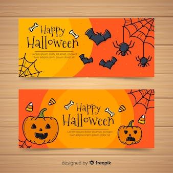 Glückliche halloween-fahnensammlung mit gezeichneten art der spinnen und der kürbise in der hand