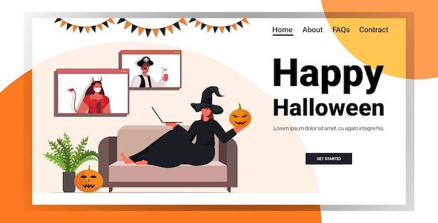 Glückliche halloween-feiertagsfeierfrau im hexenkostüm, die mit freunden während des videoanrufs diskutiert