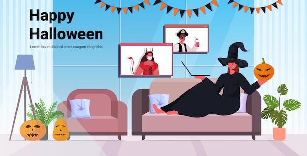 Glückliche halloween-feiertagsfeierfrau im hexenkostüm, die mit freunden während des videoanrufs wohnzimmerinnenraum diskutiert
