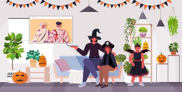 Glückliche halloween-feiertagsfeierkonzeptfamilie in kostümen, die mit großeltern während des videoanrufs wohnzimmerinnenraum diskutieren