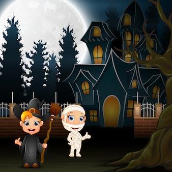 Glückliche halloween-kinder mit furchtsamem haus und vollmond