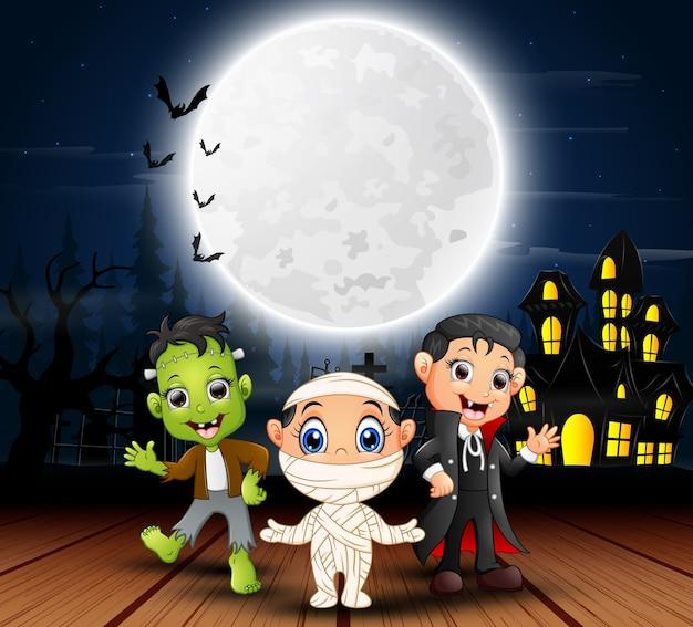 Glückliche halloween-kinder mit furchtsamem haus