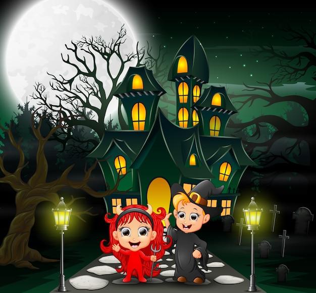 Glückliche halloween-kinder vor dem geisterhaus