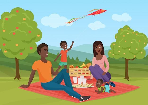 Glückliche junge afroamerikanerfamilie mit kind auf einem picknick