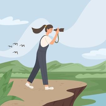 Glückliche junge frau benutzt teleskop für sighseein im wald