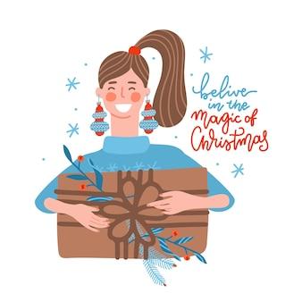 Glückliche junge frau, die ein riesiges weihnachtsgeschenkkastenmädchen mit kugelohrringen trägt, das ihre feiertagsvor...