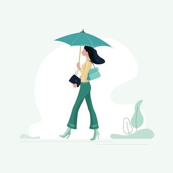 Glückliche junge frau, die geht, während sie einen regenschirm hält, sommer und regentage