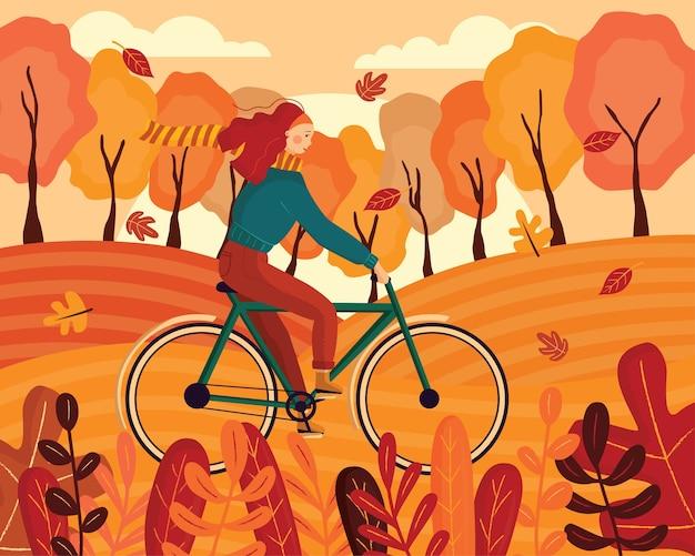 Glückliche junge frau gekleidet in herbstkleidung, die ein fahrrad in einem wald reitet