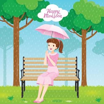 Glückliche junge frau unter regenschirm, der auf bank im park sitzt