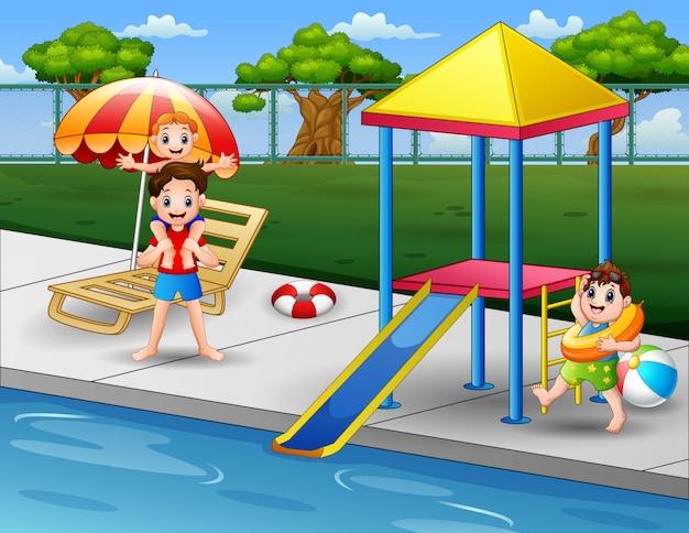 Glückliche jungen, die am poolrand im hinterhof spielen