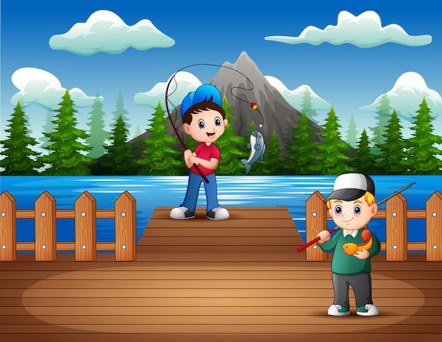 Glückliche jungen, die auf dem hölzernen pier fischen