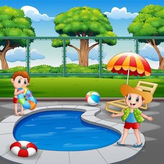 Glückliche jungen, die das spielen im außenpool genießen