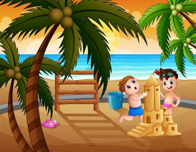 Glückliche jungen, die eine sandburg am strand machen