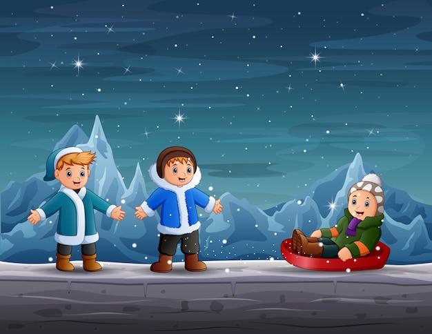 Glückliche jungen, die in der winterszene spielen