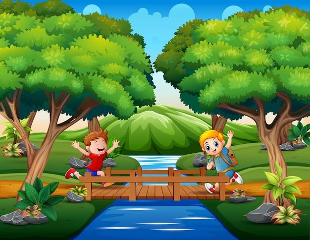 Glückliche jungen rannten über die holzbrücke