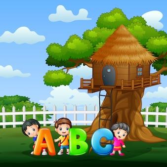 Glückliche kinder, die abc-text im park halten