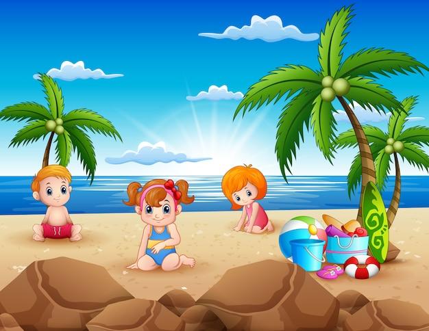 Glückliche kinder, die auf dem sandstrand sitzen