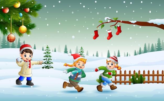 Glückliche kinder, die auf dem schnee am weihnachtstag spielen und laufen