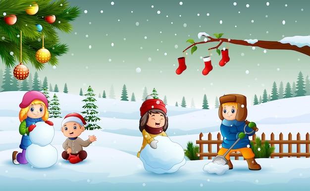 Glückliche kinder, die auf dem schnee spielen und einen schneemann am weihnachtstag machen