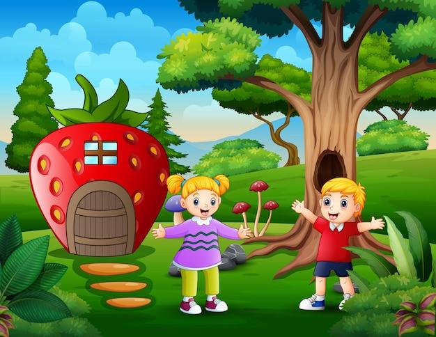 Glückliche kinder, die durch das fantasy-erdbeerhaus spielen