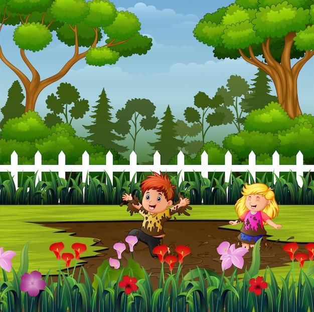 Glückliche kinder, die eine schlammpfütze im park spielen