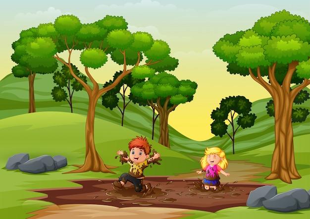 Glückliche kinder, die eine schlammpfütze in der natur spielen