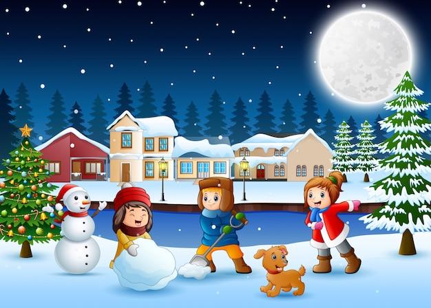 Glückliche kinder, die einen schneemann im schneebedeckten dorf machen
