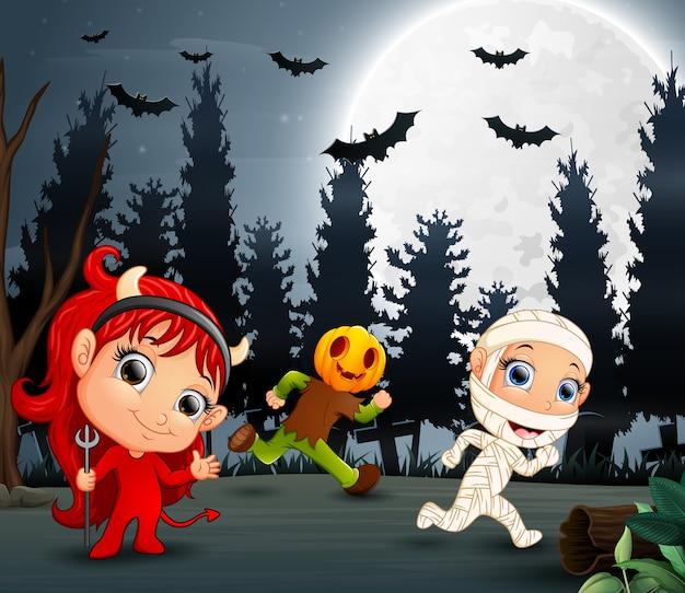 Glückliche kinder, die halloween-kostüm im garten tragen