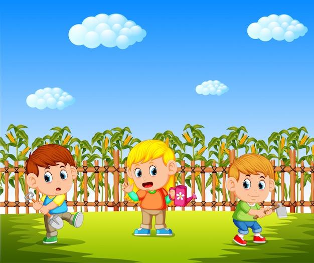 Glückliche kinder, die im maisfeld mit dem halten von gartengeräten pflanzen