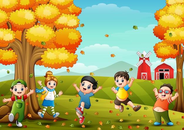 Glückliche kinder, die in der bauernhoflandschaft am herbst spielen