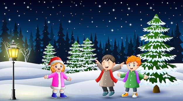 Glückliche kinder, die in der winterlandschaft nachts spielen