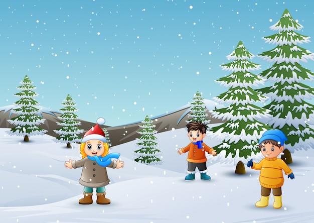 Glückliche kinder, die in der winterlandschaft spielen