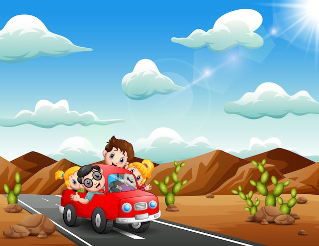 Glückliche kinder, die mit dem roten auto durch die wüste reisen