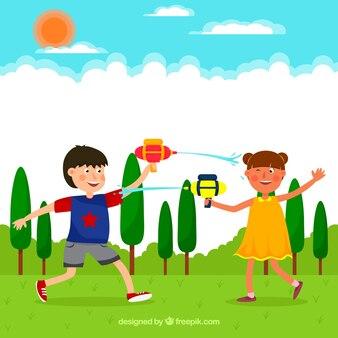 Glückliche kinder, die mit wasserwerfern im park spielen