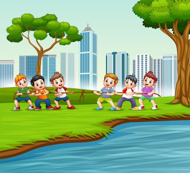Glückliche kinder, die tauziehen im stadtpark spielen