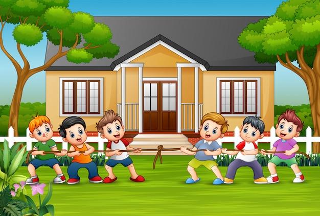 Glückliche kinder, die tauziehen in der front ein haus spielen