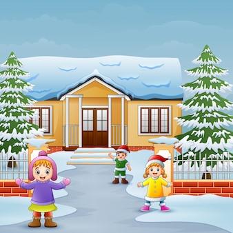 Glückliche kinder, die vor dem schneienden haus spielen