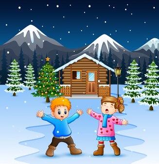 Glückliche kinder, die vor dem schneienden holzhaus spielen
