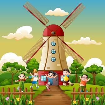 Glückliche kinder, die vor windmühlengebäudehintergrund spielen