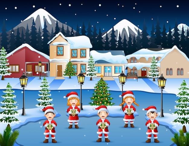 Glückliche kinder, die weihnachtslieder in der winternachtlandschaft singen
