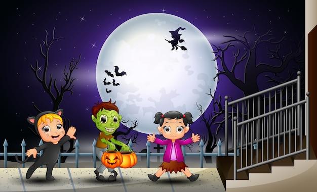 Glückliche kinder halloween im vollmondhintergrund
