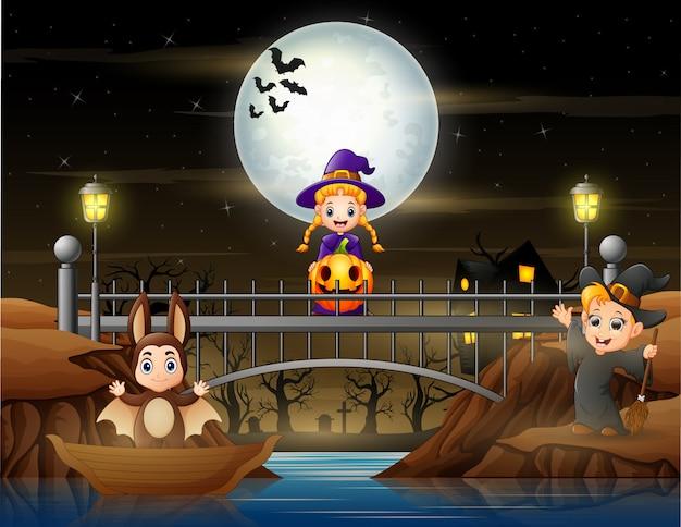 Glückliche kinder im halloween-kostüm feiern auf der brücke