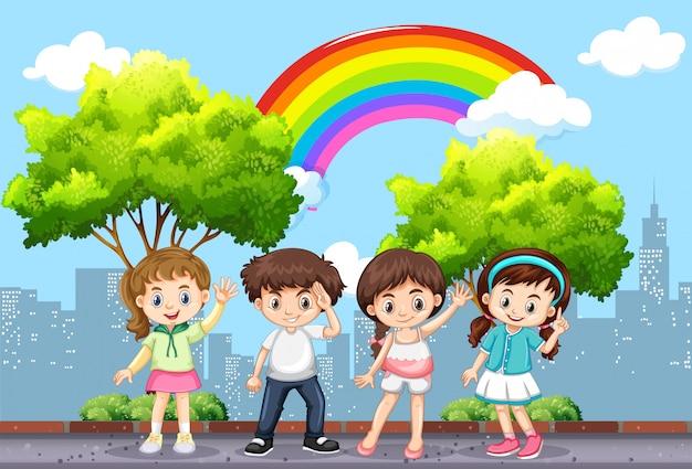 Glückliche kinder im park mit regenbogen im himmel